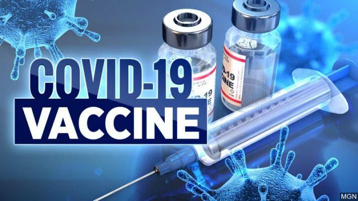"The words ""Covid-19 vaccine"" with background of blue COVID viruses, syringe, and two vaccine vials."