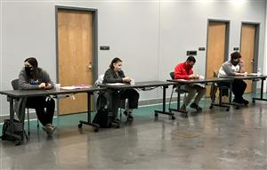 Four teachers sit at tables at CTC during workshop